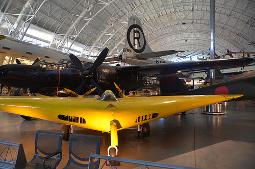 "Steven F. Udvar-Hazy Center: Yellow Northrop N1M flying wing airplane, in front of Northrop P-61C Black Widow and tail of the Boeing B-29 Superfortress ""Enola Gay"", et al"
